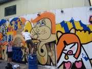 На бочке рисует на стене человек